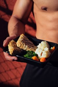 person holding cooked food on black tray