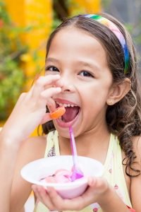 girl holding candy while putting to her mouth